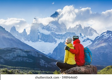Travelers couple in love enjoying the view of majestic Mount Fitz Roy - symbol of Patagonia, Argentina