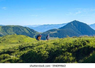 Travelers - father and son with backpacks go along a ridge on the blue sky background among green mountains. Sunny day in the mountains.