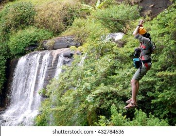 Travelers hung on a a wire rope over a vast forest, a fun and challenging activity, a zipline in bolaven plateau southern laos, hung over waterfall