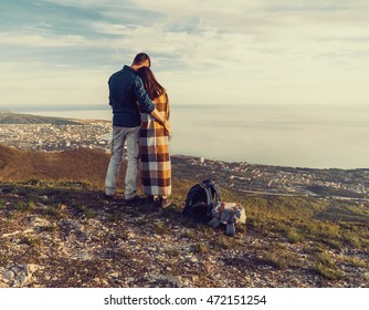 Travelers loving couple standing in the mountains and enjoying view of sea, rear view. Man embracing a woman