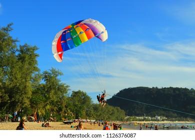 Travelers are playing colorful parasailing at Patong Beach.