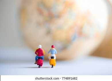 Travelers riding motorcycles with world globe using as background traveling or exploring the world, budget travel concepts.