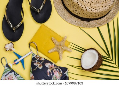 Travelers set on yellow background. Palm leaf, camera, beach straw hat, flip flop, passport and bikini. Vacation concept. Flat lay style. Copy space for text