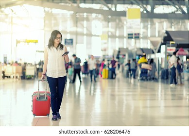 Travelers smart asian woman walking with a luggage and using smart phone  at airport terminal with blurred crowd of travelling people in background. Traveling concept.
