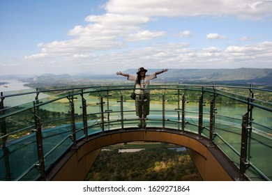 Travelers thai woman people travel visit and posing for take photo view on glass skywalk of cliffs at Wat Pha Tak Suea temple in Nongkhai, Thailand