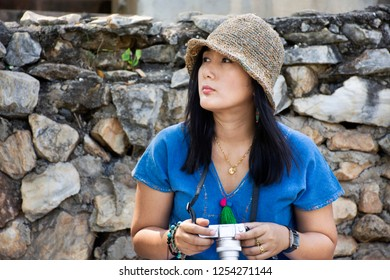 Travelers thai woman travel and sitting relax on trunk bench in garden of Pa Tueng Hot Spring at Mae Chan in Chiang Rai, Thailand