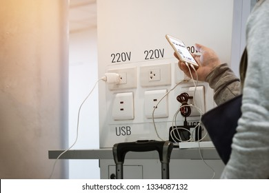 Travelers use smartphone for Charger corner free charge appliances and electronics equipment phones notebook usb / 220V socket providing tourists and travelers at Airport Thailand.