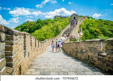 Travelers walking on the great wall of China. The construction of the wonders of the world on a mountain filled with green trees.