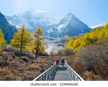 Travelers walking on walkway with snow mountains on the background in Yading Nature Reserve, Sichuan, China