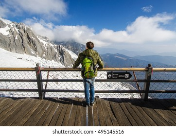 Travelers were standing looking at the snow on the mountain . Enjoy the atmosphere in front, On a bright blue sky. Jade dragon snow mount, Lijiang, yunnan, southern china,