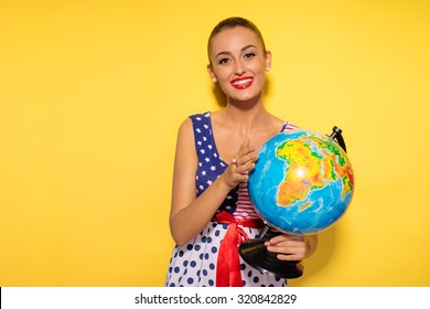 Traveling around the world. Colorful studio portrait of pretty young brunette woman holding globe sphere. Yellow background.