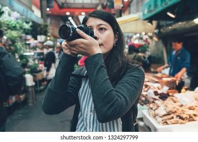 Traveling Asian female tourist backpacker take photo in kuromon ichiba market on holidays. young girl holding camera shooting in local japanese place osaka kitchen. elegant travel lady photographing
