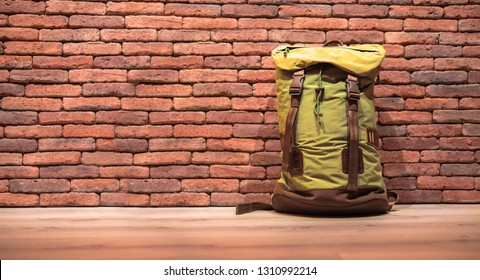 Traveling backpack resting on a wooden floor, red brick wall background