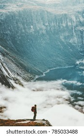 Traveling backpacker adventure Lifestyle wanderlust concept vacations outdoor hiking with backpack roam above clouds and lake in mountains