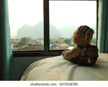 a traveling bear sitting on the bed in sight seeing room. He looking to the mountain from the glass window of hotel.
