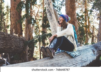 Traveling beautiful girl with backpack and knitted hat talking on mobile phone and sitting on tree in wild forest at sunny day. Smiling. Laughing.