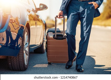 Traveling businessman with his luggage near car.