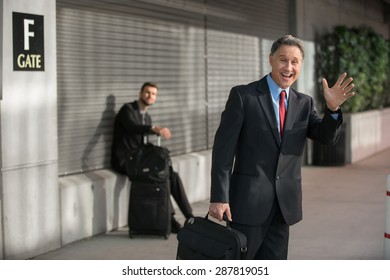 Traveling businessman with smile after arriving at the airport