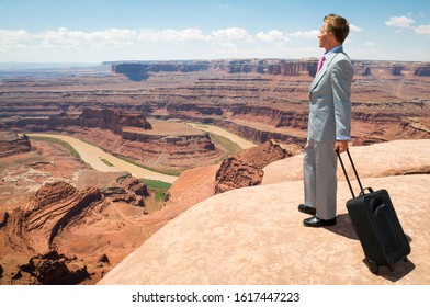 Traveling businessman standing with a wheelie carry-on suitcase looking out over massive red rock canyon landscape