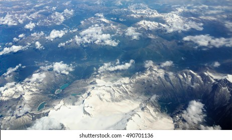 Traveling by air through an airplane window. Aerial view of Alps mountains surrounded by cirrus and cumulus clouds with little turbulence, showing Earth's atmosphere.