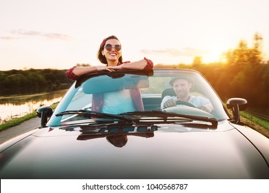 Traveling by car - couplr in love dgo by cabriolet car in sunset time