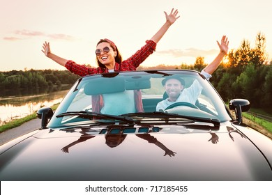 Traveling by car - happy couple in love go by cabriolet car in sunset time
