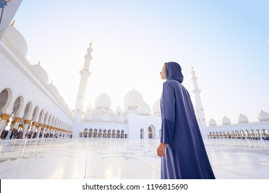 Traveling by Unated Arabic Emirates. Woman in traditional abaya standing in the Sheikh Zayed Grand Mosque, famous Abu Dhabi sightseeing.