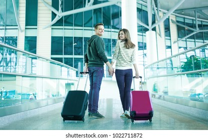 Traveling concept. Back view of loving couple with hand luggage in airport terminal.