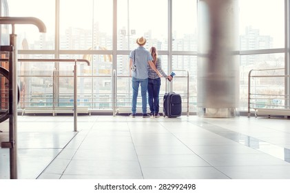 Traveling concept. Back view of loving couple in casual wear standing near the window of international airport terminal.