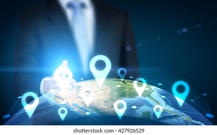 Traveling concept with businessman pointing at globe with location pin network on dark background. Elements of this image furnished by NASA