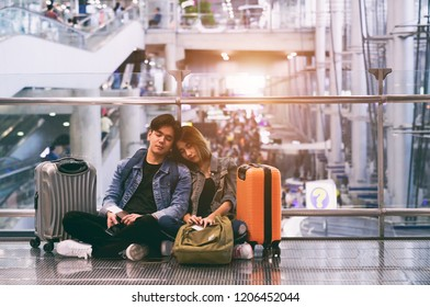 Traveling concept. Happy Asian couple asleep waiting for boarding in airport holding passport with tickets and luggage.