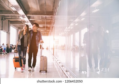 Traveling concept. Happy Asian couple  waiting for boarding in casual wear walking in airport holding passport with tickets and luggage.
