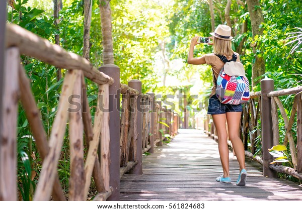 Traveling concept. Photographing adventure. Young woman taking picture on her smartphone in jungle.