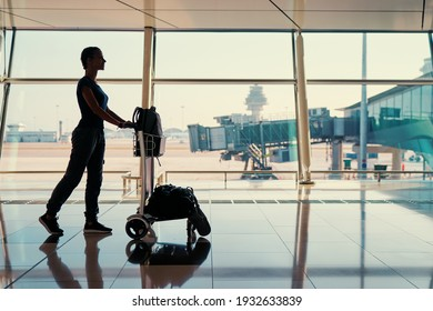 Traveling concept. Silhouette of young woman with baggage in international airport terminal.