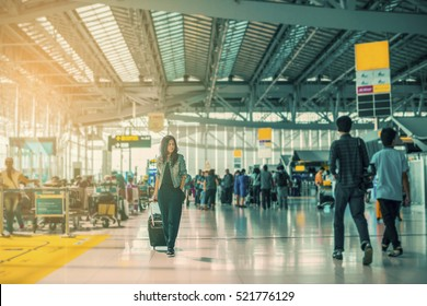 Traveling concept. Travelers asian woman walking with a luggage at airport terminal and airport terminal blurred crowd of travelling people on the background. (vintage color tone, advertise concept)