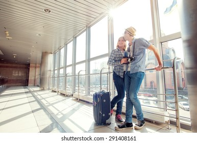 Traveling concept. Waiting for boarding. Happy loving couple in casual wear standing in airport terminal holding passport with tickets.