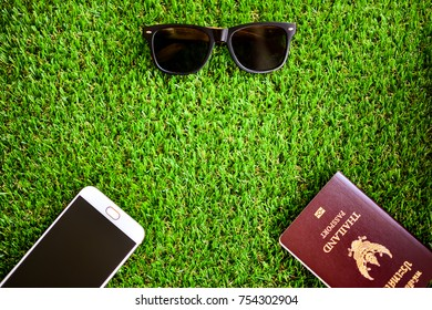 Traveling concepts : Mobile phone , passport and sun glasses on green grass with copy space. Soft focus.