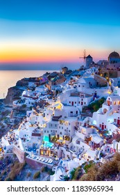 Traveling Concepts. Panoramic View of Famous Old Town of Oia or Ia at Santorini Island in Greece. Taken During Blue Hour with Traditional White Houses and Windmills.Vertical image