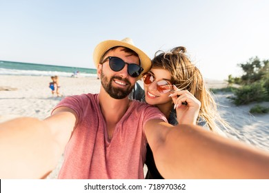 Traveling couple in love   making self portrait by digital camera , having fun on  amazing tropical beach.   Attractive wonder girl with   stylish hipster boyfriend enjoying holidays.