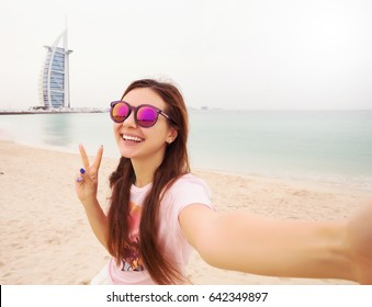 Traveling in Dubai. Pretty young woman in swimsuit taking selfie on the beach .Prettyyoung female tourist takes travel selfie at the beach while summer vacation.