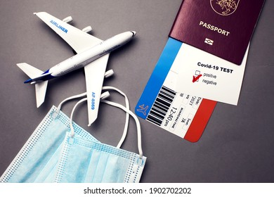 Traveling during COVID-19 pandemic, passport with airline ticket, covid-19 negative test, medical masks and plane on grey background, airport security health and safety check concept - Shutterstock ID 1902702202