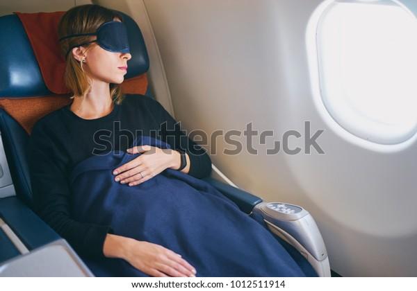 一等旅。快適な逃避。機内で寝ている美しい若い女性。