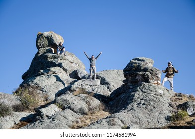 Traveling friends climbing the big rocks in Marcahuasi located east of the city of Lima - Peru
