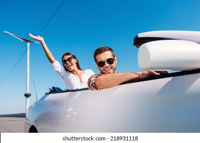 Traveling with fun. Happy young couple enjoying road trip in their convertible while woman raising arms and smiling