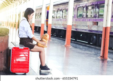 Traveling with a girl waiting for  train with a brown bear