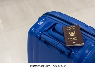 Traveling luggage in airport terminal with thai passport. Travel concept.