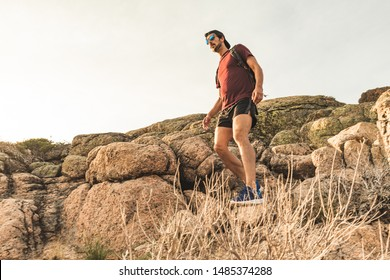 Traveling Man tourist with backpack hiking in mountains landscape active healthy lifestyle adventure vacations on rocky mountain.