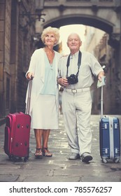 Traveling mature spouses standing in front of old cathedral with a map and camera
