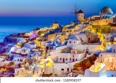 Traveling and New Destinations Concepts.Romantic Sunset at Santorini Island in Greece. Image Taken in Oia Village At Dusk.Amazing Sunset with White Houses and Windmills in Frame.Horizontal Orientation