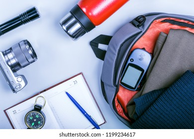 Traveling - packing (preparing) for adventure trip concept. Backpack, compas, notebook, navigator or phone, thermos and camera on wooden background captured from above (flat lay).